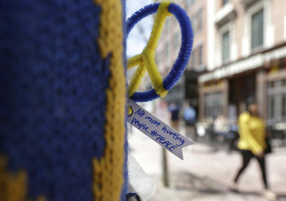 A peace symbol and a message are attached to a lamp post near one of two blast sites close to the finish line of the Boston Marathon, Wednesday, April 15, 2015, in Boston. Boston is marking the second anniversary of the 2013 marathon bombings. (AP Photo/Steven Senne)