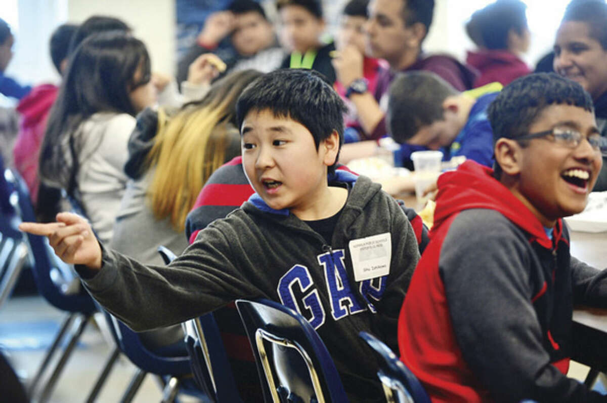 Hour photo / Erik Trautmann Japanese student Shu Ishikawa converses with other students during lunchtime as Ponus Ridge Middle School hosts nine students from the Greenwich Japanese School on Thursday.