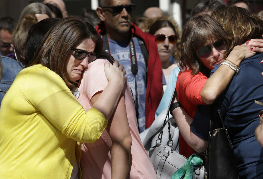 Jenna Dziedzic, of Boston, left, hugs Sabrina Dellorusso, also of Boston, second from left, as Linda Witt, of Neenah, Wis., second from right, hugs Jillian Boynton, of Manchester, N.H., right, during a moment of silence at one of two blast sites near the finish line of the Boston Marathon, in Boston, Wednesday, April 15, 2015. All four women were near the finish line of the Boston Marathon in 2013 where a friend, Roseann Sdoia, lost a limb during the explosion. (AP Photo/Steven Senne)