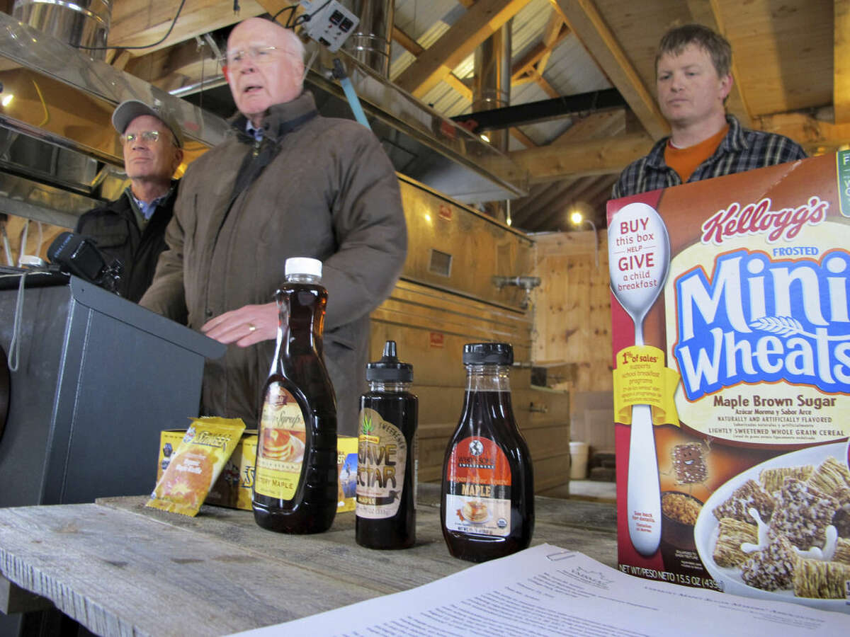 """Maple sugar producer Burr Morse, left, is joined by U.S. Sen. Patrick Leahy, D-Vt., center, and Roger Brown, of Slopeside Syrup, right as they talk about a request by maple producers that the Food and Drug Administration crack down on food producers who use """"maple"""" in their labeling when there isn't any syrup in their products, during an event Tuesday, Feb. 16, 2016, in Richmond, Vt. In a letter to the FDA, Vermont producers were joined by maple associations from Maine to Wisconsin who want the FDA to take enforcement action to either remove the maple branding from the products or have the companies add maple syrup to them. (AP Photo/Lisa Rathke)"""