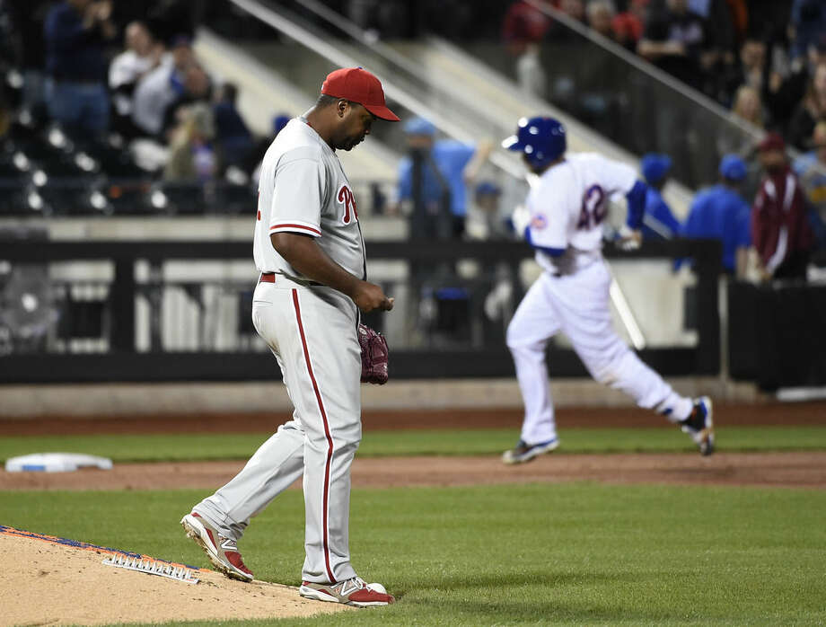 Philadelphia Phillies starting pitcher Jerome Williams, left, reacts on the mound as New York Mets Travis d'Arnaud rounds third base after hitting a solo home run in the third inning of a baseball game at Citi Field on Wednesday, April 15, 2015, in New York. (AP Photo/Kathy Kmonicek)