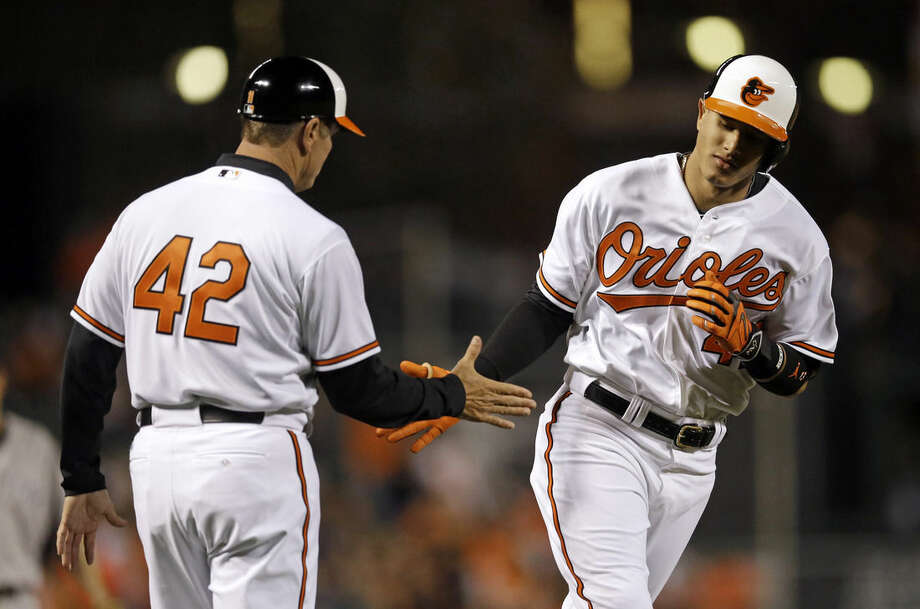 Baltimore Orioles' Manny Machado, right, greets third base coach Bobby Dickerson as he rounds the bases on a solo home run in the fourth inning of a baseball game against the New York Yankees, Wednesday, April 15, 2015, in Baltimore. (AP Photo/Patrick Semansky)