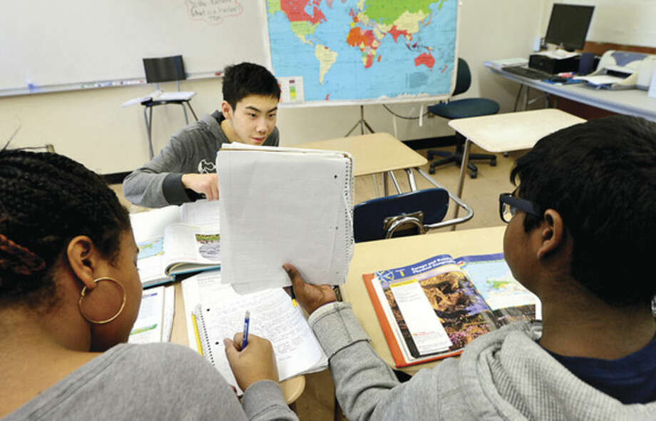 Hour photo/Erik TrautmannPonus Ridge Middle School seventh-graders Sidney Seide and Brandon Das help Japanese student Takaya Kodama as Ponus hosts nine students from the Greenwich Japanese School on Thursday. Ponus Ridge Japanese teacher, Mrs. Misae Pergolizzi, has established a relationship with the school to help foster student interest in the school's Japanese language program.