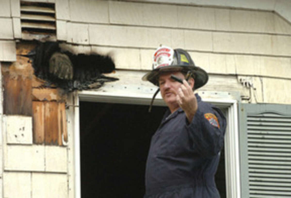 Hour Photo/Alex von Kleydorff In this 2013 file photo, Deputy Fire Marshal Chris Hansen holds an object of interest while inspecting the cause of a fire.