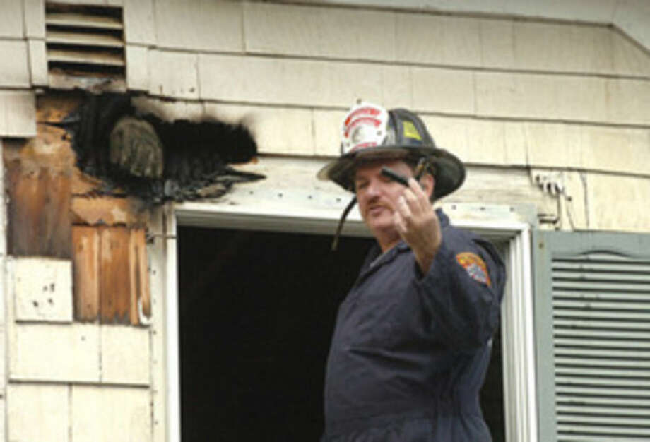 Hour Photo/Alex von KleydorffIn this 2013 file photo, Deputy Fire Marshal Chris Hansen holds an object of interest while inspecting the cause of a fire.