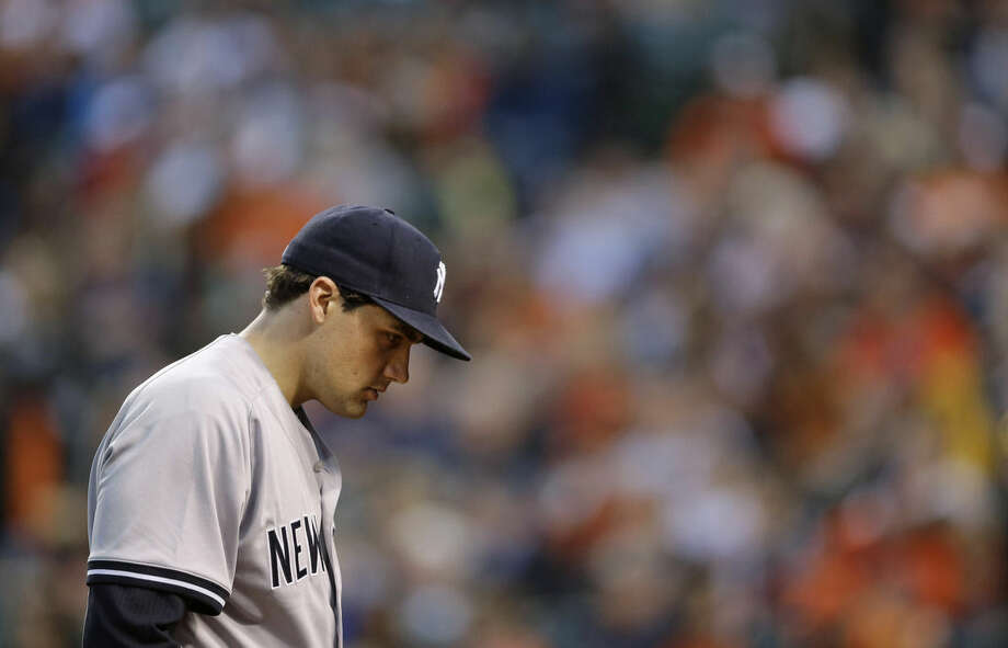 New York Yankees starting pitcher Nathan Eovaldi walks off the field at the end of the first inning of a baseball game against the Baltimore Orioles, Wednesday, April 15, 2015, in Baltimore. Baltimore scored a run against Eovaldi in the first. (AP Photo/Patrick Semansky)