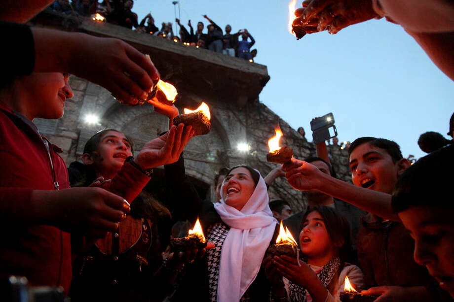 In this Tuesday, April 15, 2015 photo, Yazidis gather at the holy shrine of Lalish, 57 kilometers (35 miles) north of militant-held Mosul, Iraq, as thousands celebrate the New Year, their first since Islamic State militants swept through the area last summer. The Islamic State militants view Yazidis as apostates, departing from their radical interpretation of Islam, and demanded that they convert to Islam or pay a religious fine. (AP Photo/Seivan M.Salim)