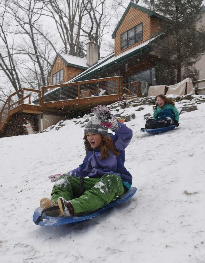 Phoebe Davidson, front, 9, and her friend Helena McConatha Rosle, 10, slide down the hill in front of Phoebe's house Monday, Feb. 15, 2016, in Media, Pa. (Clem Murray/The Philadelphia Inquirer via AP)