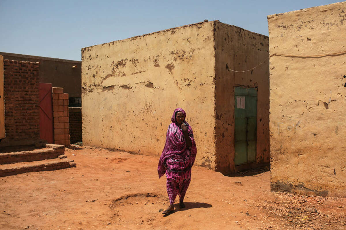 In this picture taken Tuesday, April 14, 2015, a Sudanese woman walks outside her home in Izba, an impoverished neighborhood, on the outskirts of Khartoum, Sudan. Izba is one sign of how the constant internal wars, under Sudan's President Omar al-Bashir, have shaped, Khartoum. Before al-Bashir came to power, Izba was home to a community of Arab tribesmen who had settled here to be close to the capital. But through the 1990s and 2000s, it swelled with Sudanese fleeing war zones around the country. Now 70,000 people live crammed into Izba, an area of about a square mile. (AP Photo/Mosa'ab Elshamy)