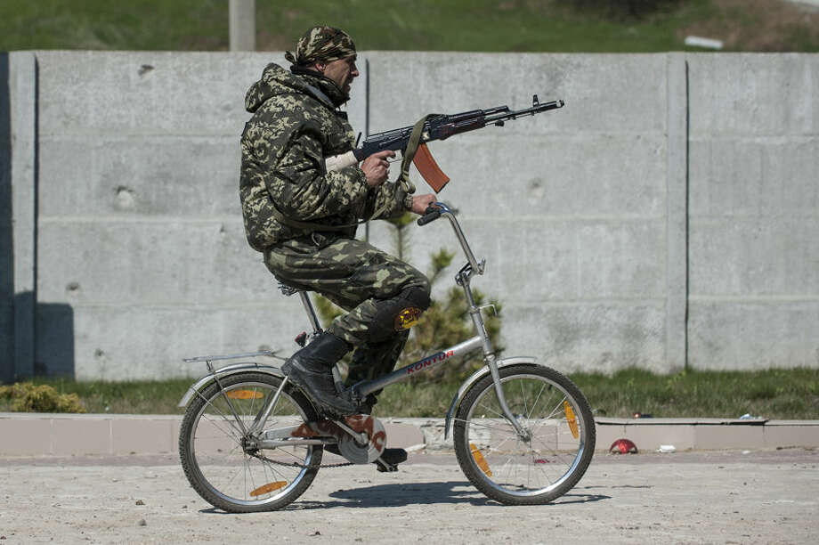 A Ukrainian serviceman rides a bicycle in Shyrokyne, eastern Ukraine, Wednesday, April 15, 2015. Russia and Ukraine agreed in Berlin on Monday to call for the pullback of smaller-caliber weapons from the front lines of the conflict that has claimed more than 6,000 lives. (AP Photo/Evgeniy Maloletka)