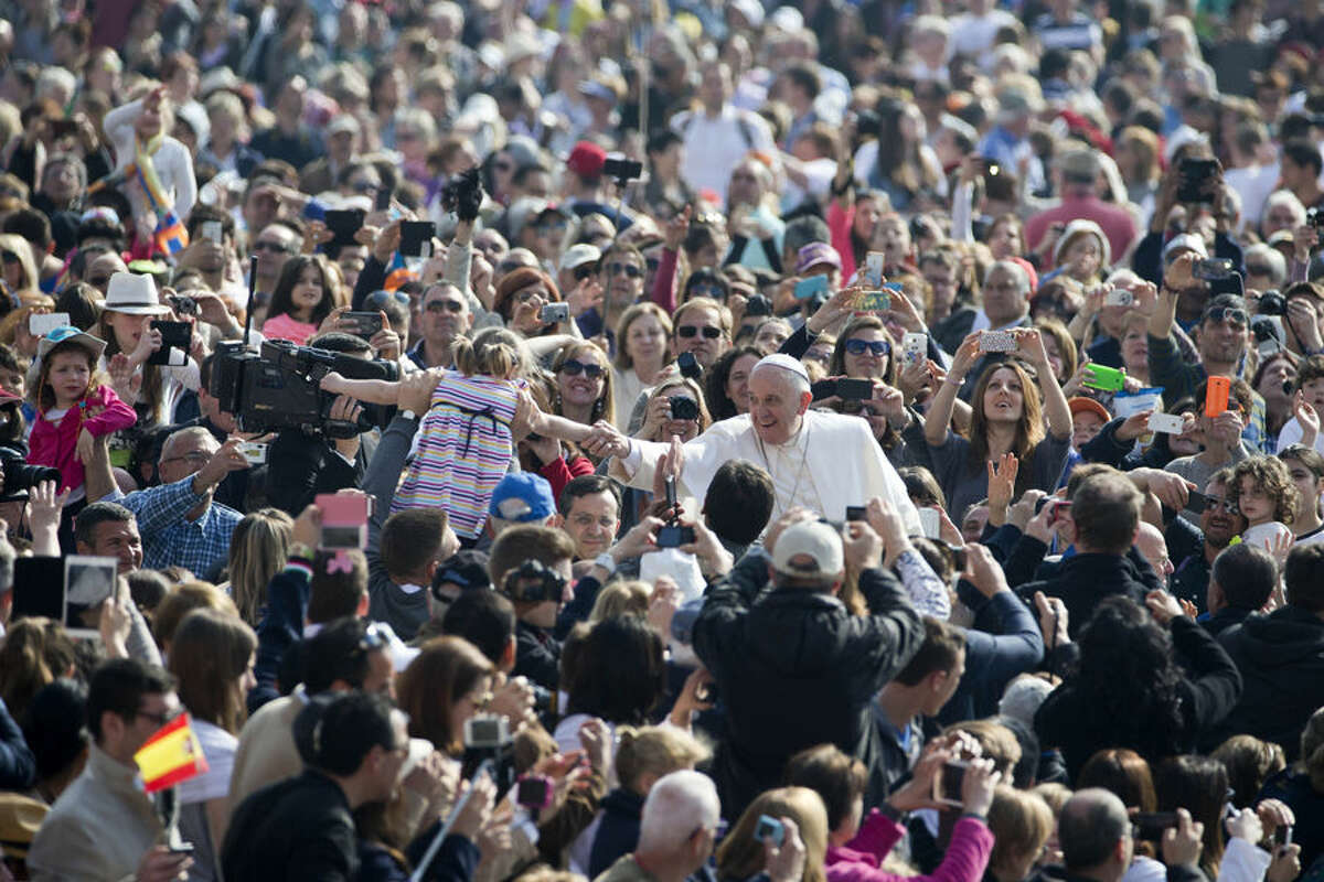 Pope Francis, center, greets a child as he arrives for his weekly general audience, in St. Peter's Square, at the Vatican, Wednesday, April 15, 2015. (AP Photo/Andrew Medichini)