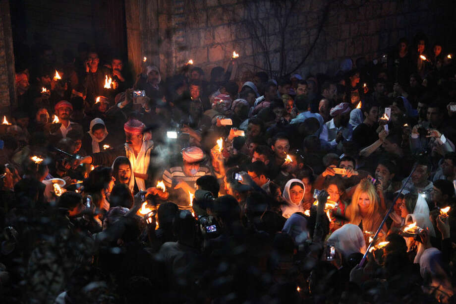 In this Tuesday, April 15, 2015 photo, Yazidis gather to light flames, some capturing the scene with their mobile phones, at the holy shrine of Lalish, 57 kilometers (35 miles) north of militant-held Mosul, Iraq, as thousands celebrate the New Year, their first since Islamic State militants swept through the area last summer. Yazidis, a centuries-old religion derived from Zoroastrianism, Christianity and Islam, believe that the occasion marks the creation of the earth, also the day that God created the holy shrine in Lalish. (AP Photo/Seivan M.Salim)