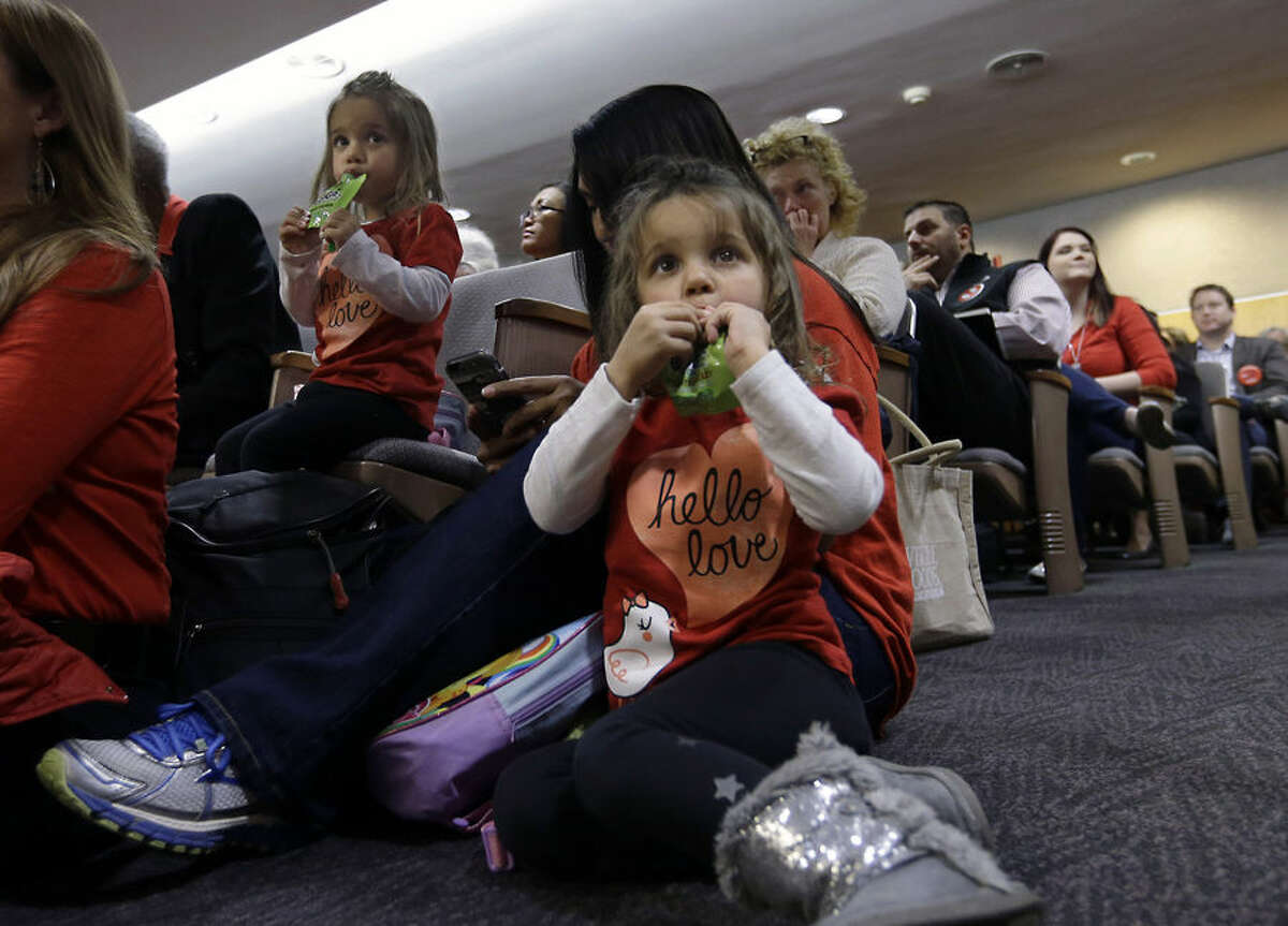 Ashley Wooledge, front, sits near her mother, Vicki, middle, and twin sister, Lexi, left, at the Senate Education Committee during discussion of a measure require California schoolchildren to get vaccinated, Wednesday, April 15, 2015, at the Capitol in Sacramento, Calif. The bill authors, Sen. Richard Pan, D-Sacramento, and Sen. Ben Allen, D-Santa Monica, agreed to postpone a vote until next week after lawmakers expressed concerns about the unvaccinated children's rights to education. (AP Photo/Rich Pedroncelli)