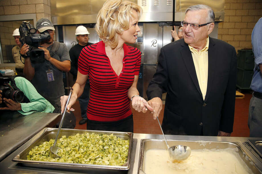 Actress Pamela Anderson, left, chats with Maricopa County Sheriff Joe Arpaio as they prepare to serve the first all-vegetarian meals to inmates at the Maricopa County Jail Wednesday, April 15, 2015, in Phoenix. Anderson, a PETA honorary director and long-time vegan, also toured Tent City after serving meals to the inmates. (AP Photo/Ross D. Franklin)