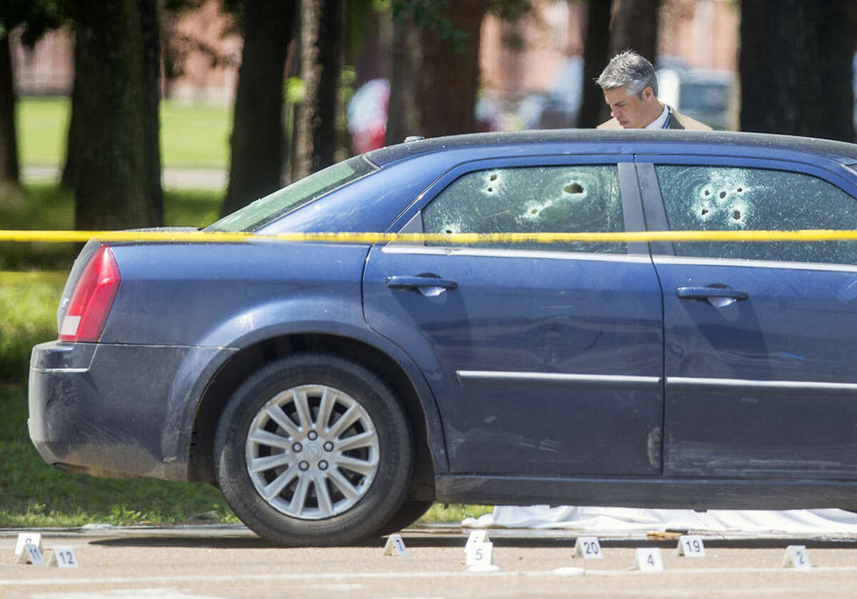 The Harris County Sheriff's Department investigates the scene of a car chase that ended in a fatal shooting Wednesday, April 15, 2015, in Houston. Deputy Thomas Gilliland, said that after the chase, two Houston police officers told the suspect to show his hands, but as they approached his car he reached back into his vehicle. Suspecting that he was reaching for a weapon, both officers opened fire multiple times, killing the man. (Cody Duty/Houston Chronicle via AP)