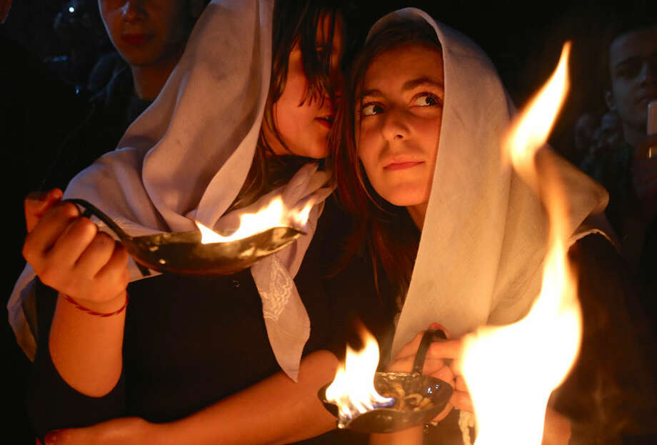 In this Tuesday, April 15, 2015 photo, a Yazidi woman whispers into the ear of her friend as both hold small fires to make a wish for the Yazidi new year, at the holy shrine of Lalish, 57 kilometers (35 miles) north of the militant-held Mosul, Iraq. With thousands of loved ones gone _ kidnapped or killed by militants with the Islamic State group _ and thousands more displaced from their homes, it was a solemn occasion commemorated with religious chants and a wish for the new year. (AP Photo/Bram Janssen)