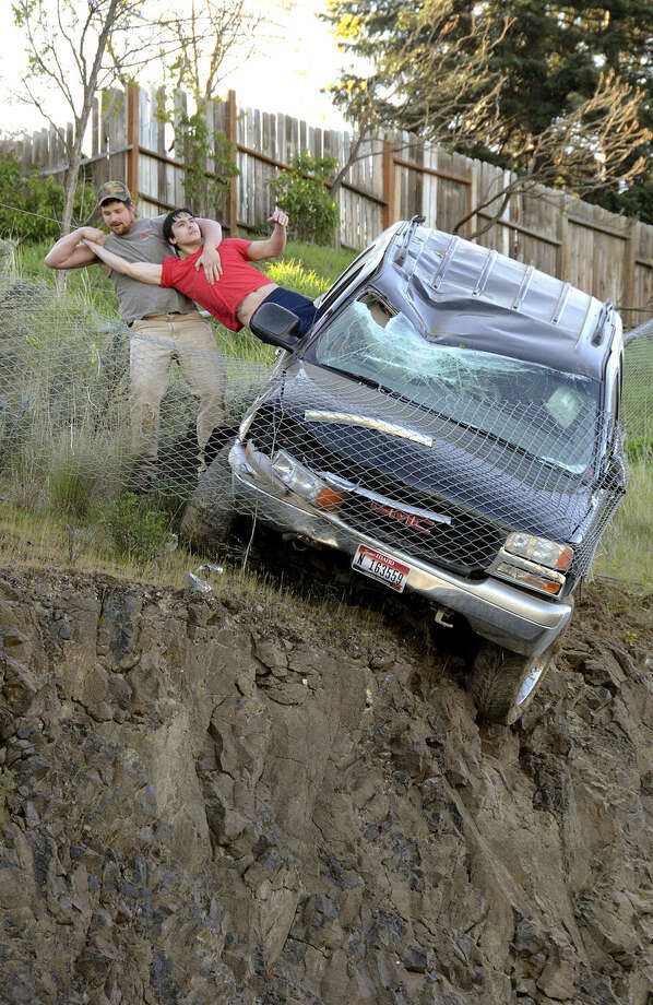 An unidentified passer-by pulls the driver from a SUV to safety after the vehicle left Mayfair Drive, traveled downhill and was stopped by a chain link fence just short of a 30-foot vertical drop onto the Bryden Canyon Road, Wednesday, April 15, 2015, in Lewiston, Idaho. (Barry Kough/Lewiston Tribune via AP)