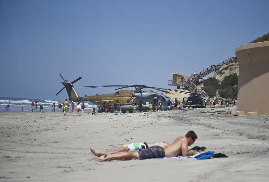 A Marine Corps helicopter sits in the sand where it made an emergency landing Wednesday, April 15, 2015 in Solana Beach, Calif. The CH-53E Super Stallion landed on the shore of this northern San Diego County town shortly after 11:30 a.m. after a low oil-pressure indicator light went on in the cockpit, Marine Corps Air Station Miramar said in a statement. (AP Photo/Lenny Ignelzi)