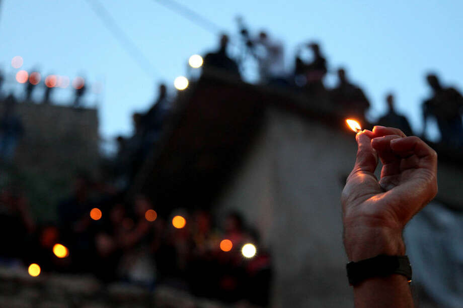 In this Tuesday, April 15, 2015 photo, a man lights a candle in the holy shrine of Lalish, 57 kilometers (35 miles) north of militant-held Mosul, Iraq, as thousands of Yazidis celebrate the New Year, which is their first since Islamic State militants swept through the area in June, 2014. They Yazidi new year starts on the first Wednesday of April according to the eastern calendar, which is thirteen days behind of the Gregorian calendar.(AP Photo/Seivan M. Salim)
