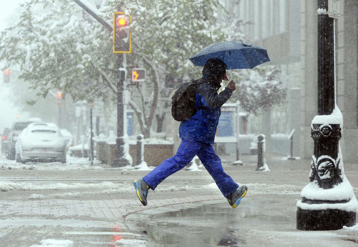 A person jumps over a puddle near Main St. in Salt Lake City, Wednesday, April 15, 2015. A spring storm has dumped 2.3 inches of snow in Salt Lake City after the winter proved to be the least snowy ever recorded. (Al Hartmann/The Salt Lake Tribune via AP)
