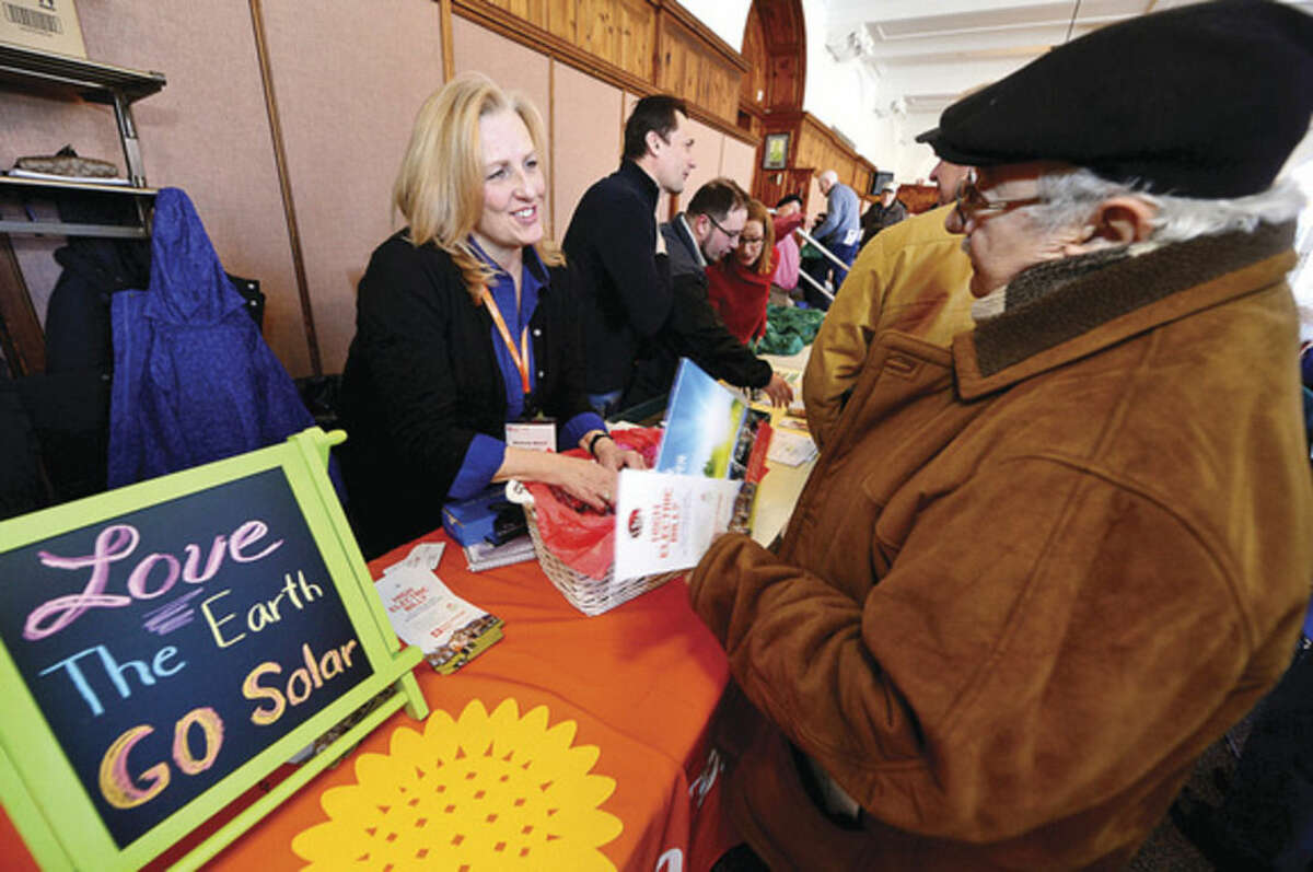 Hour photo/Erik Trautmann Barbara Welch, team leader at Direct Energy Solar, passes out information to Norwalk seniors during the Norwalk Senior Tax Relief Workshop in the City Hall Community Room Saturday.
