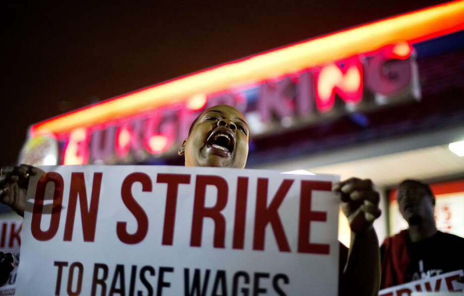 Fast food worker Qiana Shields chants during a demonstration outside a Burger King restaurant calling for the federal minimum wage to be raised to $15, Wednesday, April 15, 2015, in College Park, Ga. Organizers say they chose April 15, tax day, to demonstrate because they want the public to know that many low-wage workers must rely on public assistance to make ends meet. (AP Photo/David Goldman)