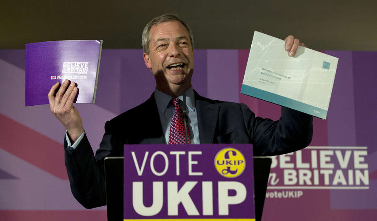 Nigel Farage leader of the UK Independence Party holds up his party's election manifesto, left, and economic policy review, right, during its launch at a media event in Thurrock, England, Wednesday, April 15, 2015. The UK goes to the polls in a General Election on May 7. (AP Photo/Alastair Grant)