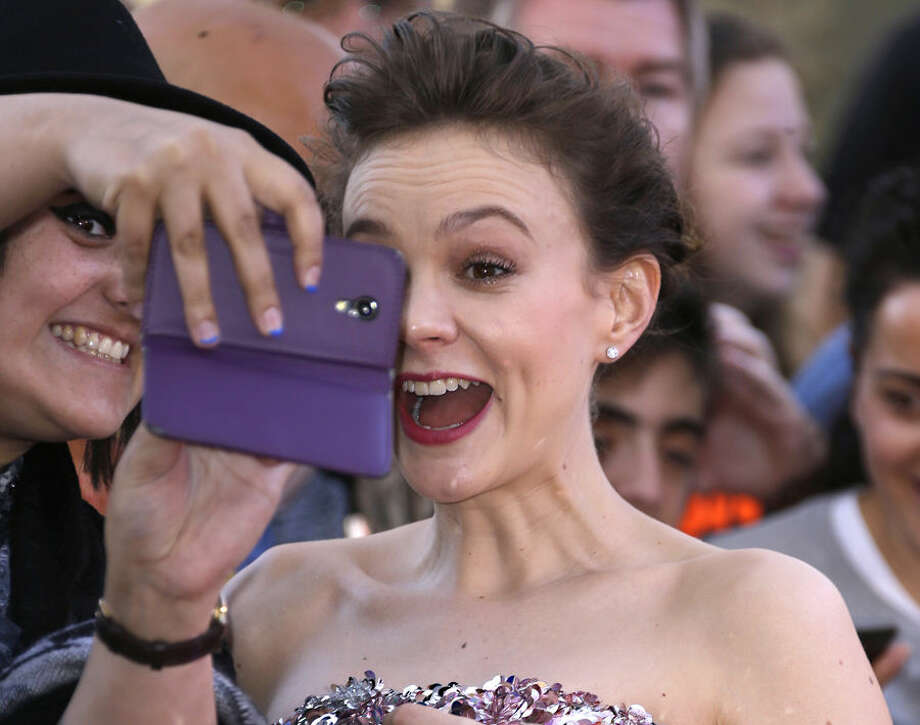 Actress Carey Mulligan reacts as she has a picture taken with a fan upon arrival at the the World premiere of the film Far From The Madding Crowd in central London, Wednesday April 15, 2015. (Photo by Joel Ryan/Invision/AP)
