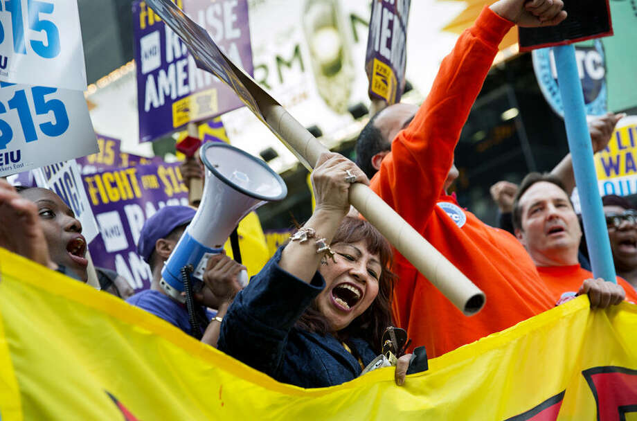 Protestors yell out during a rally and march as participants, fast food workers and union members, call for a $15 minimum wage in New York's Times Square, Wednesday, April 15, 2015. (AP Photo/Craig Ruttle)