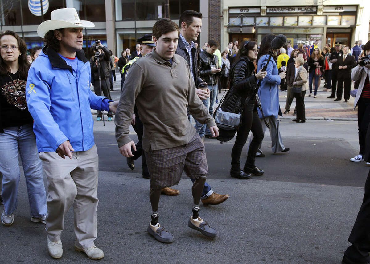 Boston Marathon survivor Jeff Bauman, right, walks past one of two blast sites with Carlos Arredondo, who helped save his life, near the finish line of the Boston Marathon in Boston, Wednesday, April 15, 2015. Boston marked the second anniversary of the 2013 marathon bombings with a subdued remembrance that includes a moment of silence, the pealing of church bells and a call for kindness. (AP Photo/Charles Krupa)