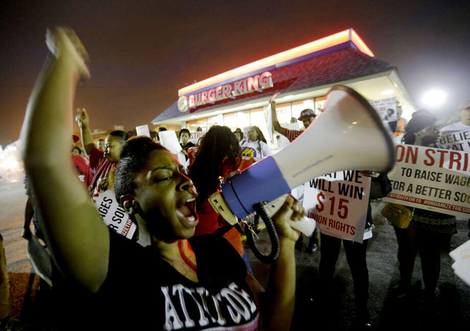 Carmen Burley-Rawls chants during a protest outside a Burger King restaurant by fast-food workers and activists calling for the federal minimum wage to be raised to $15, Wednesday, April 15, 2015, in College Park, Ga. Organizers say they chose April 15, tax day, to demonstrate because they want the public to know that many low-wage workers must rely on public assistance to make ends meet. (AP Photo/David Goldman)