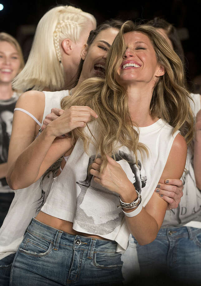 Brazilian supermodel Gisele Bundchen, front, celebrates with fellow Brazilian model Fernanda Tavares at the end of the show from the Colcci Summer collection at Sao Paulo Fashion Week in Sao Paulo, Brazil, Wednesday, April 15, 2015. Bundchen, the Brazilian supermodel who has lit up catwalks around the world for 20 years, is retiring from the runway. (AP Photo/Andre Penner)
