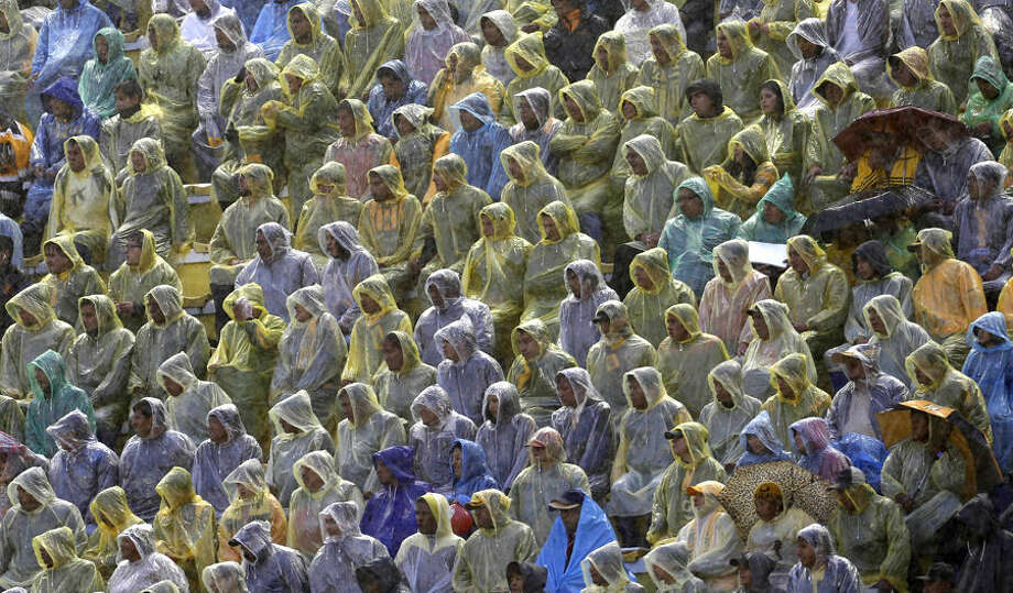 Fans of Bolivia's The Strongest, cheer for their team as they cover themselves from the rain with plastic ponchos during the Copa Libertadores soccer match against Ecuador's Emelec in La Paz, Bolivia, Wednesday, April 15, 2015. The Strongest won 1-0. (AP Photo/Juan Karita)