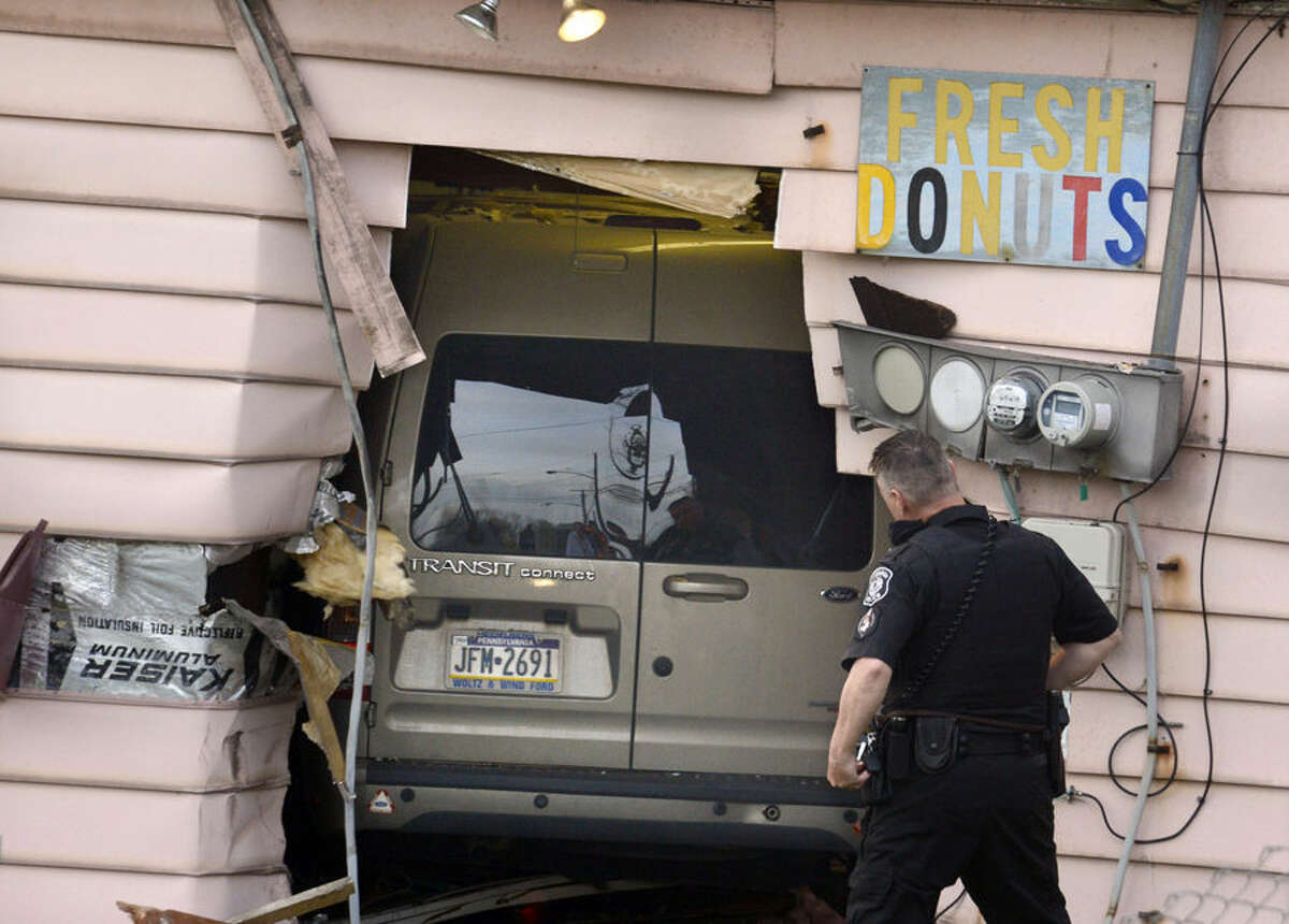 A police officer investigates a vehicle that crashed into the Better-Maid Donut shop, Wednesday, April 15, 2015, in Pittsburgh. Police didn't immediately release the names of the customers or the driver, but say one customer was pinned against a wall and another hurt her ankle. Police say the driver will be cited after apparently driving too fast and losing control shortly after 7 a.m. (Darrell Sapp/Pittsburgh Post-Gazette via AP) MAGS OUT; NO SALES; MONESSEN OUT; KITTANNING OUT; CONNELLSVILLE OUT; GREENSBURG OUT; TARENTUM OUT; NORTH HILLS NEWS RECORD OUT; BUTLER OUT