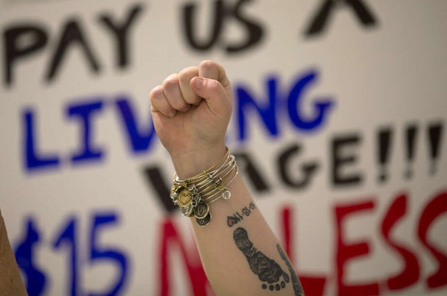 A fast-food worker raises her fist during a rally for a $15 an hour wage at the Empire State Plaza Concourse, Wednesday, April 15, 2015, in Albany, N.Y. Airport workers, home care workers, Walmart workers and adjunct professors are among those set to join in the Fight for $15 protests across the country, in what organizers are calling the biggest ever mobilization of workers in the U.S. (AP Photo/Mike Groll)