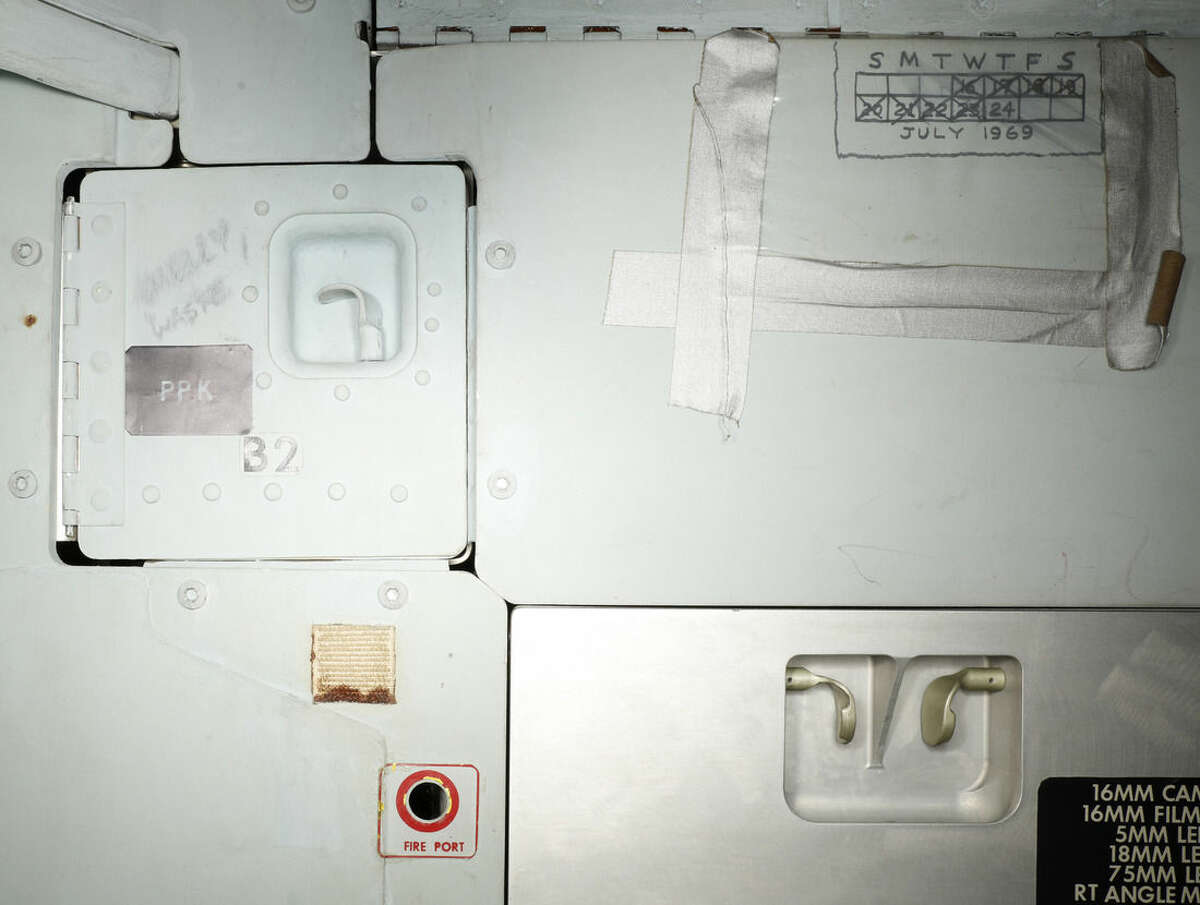This image provided by the Smithsonian Institution shows part of the interior of the Apollo 11 command module that shows graffiti left by astronauts Neil Armstrong, Buzz Aldrin and Michael Collins. A calendar hand drawn on the wall marking days in space and scribbled warning instructions to not open certain doors are some of the things the public will be able to see as part of a new, 3D look inside the spacecraft that took astronauts on America's historic 1969 mission to the moon. (Smithsonian Institution via AP)