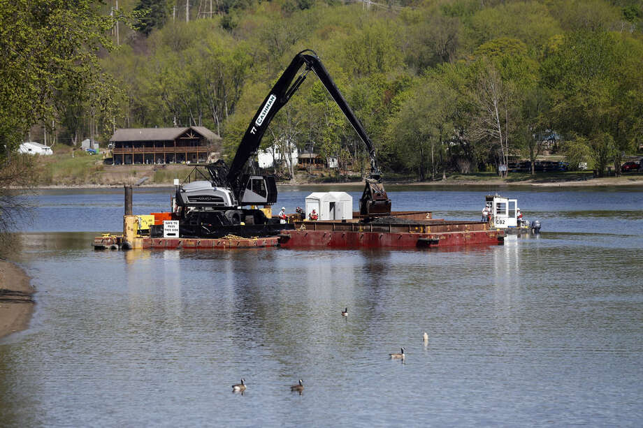 FILE - In this May 7, 2015, file photo, crews perform dredging work along the upper Hudson River in Waterford, N.Y. Dredging operations on the upper Hudson River have wound down after six years and some $1.5 billion in costs, but the push to expand the cleanup continues. (AP Photo/Mike Groll, File)