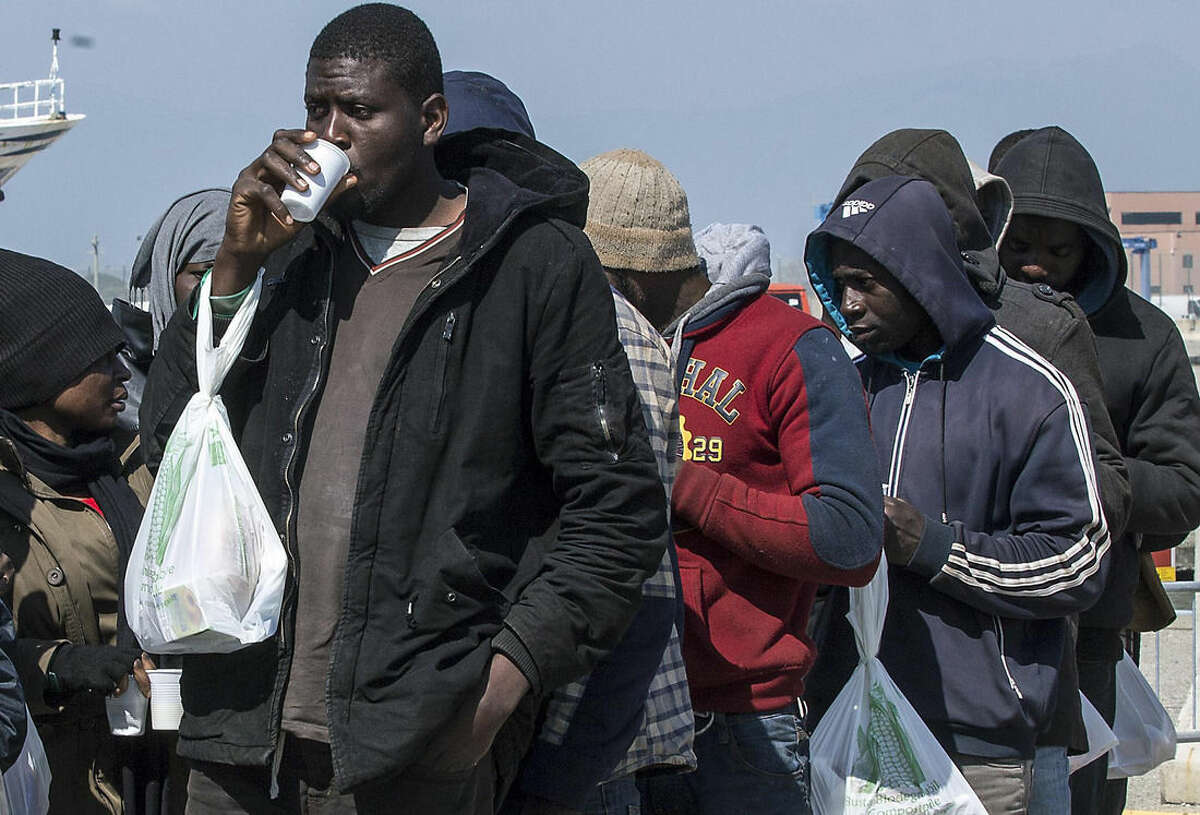 Rescued migrants line up after disembarking at the southern Italian port of Corigliano, Italy, Wednesday, April 15, 2015. Survivors of a capsized migrant boat off Libya have told Tuesday, April 14, the aid group Save the Children that an estimated 400 people are believed to have drowned. Even before the survivors were interviewed, Italy's Coast Guard said it assumed that there were many dead given the size of the ship and that nine bodies had been found. (Francesco Arena, ANSA via AP)