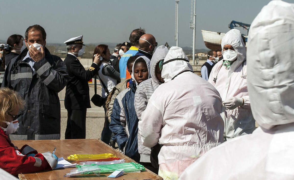 Rescued migrants arrive at the southern Italian port of Corigliano, Italy, Wednesday, April 15, 2015. Survivors of a capsized migrant boat off Libya have told Tuesday, April 14, the aid group Save the Children that an estimated 400 people are believed to have drowned. Even before the survivors were interviewed, Italy's Coast Guard said it assumed that there were many dead given the size of the ship and that nine bodies had been found. (Francesco Arena, ANSA via AP)