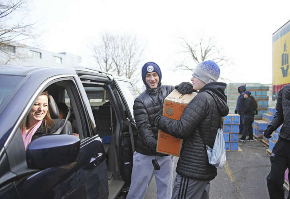 Hour photo/Danielle Calloway Dylan Honing and Jake Leon load Nella Gonzalez's car with cookies during a statewide cookie drop hosted by Girls Scouts of America at Norden Park in Norwalk Saturday morning.