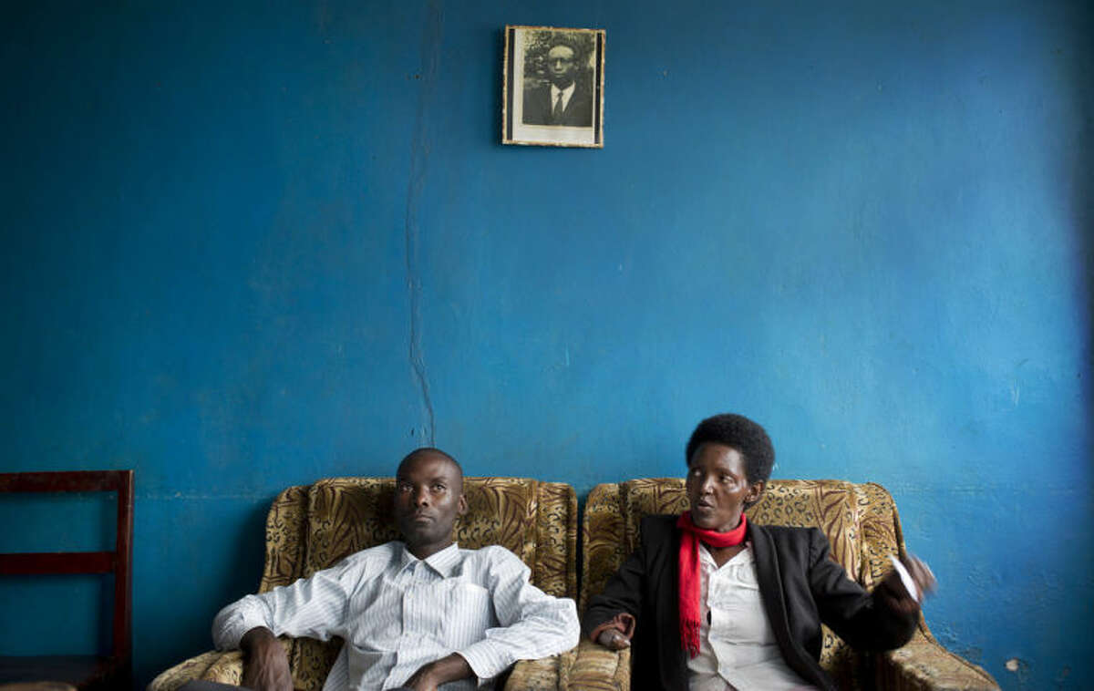 In this photo taken Wednesday, March 26, 2014, Emmanuel Ndayisaba, left, and Alice Mukarurinda, recount their experiences of the Rwandan genocide as they sit under a photograph of Alice's father, who was elsewhere at the time and also managed to survive, at Alice's house in Nyamata, Rwanda. She lost her baby daughter and her right hand to a manic killing spree. He wielded the machete that took both. Yet today, despite coming from opposite sides of an unspeakable shared past, Alice Mukarurinda and Emmanuel Ndayisaba are friends. She is the treasurer and he the vice president of a group that builds simple brick houses for genocide survivors. They live near each other and shop at the same market. Their story of ethnic violence, extreme guilt and, to some degree, reconciliation is the story of Rwanda today, 20 years after its Hutu majority killed more than 1 million Tutsis and moderate Hutus. The Rwandan government is still accused by human rights groups of holding an iron grip on power, stifling dissent and killing political opponents. But even critics give President Paul Kagame credit for leading the country toward a peace that seemed all but impossible two decades ago. (AP Photo/Ben Curtis)
