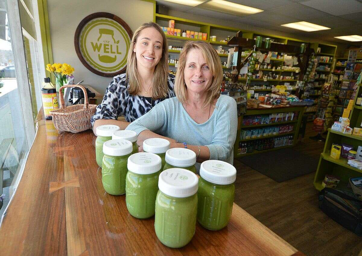 """Kathy Helms, owner of The Well in Wilton, and Kaitlin Creahan, the store manager, with some of their """"Glowing Green"""" natural cleanse smoothies."""