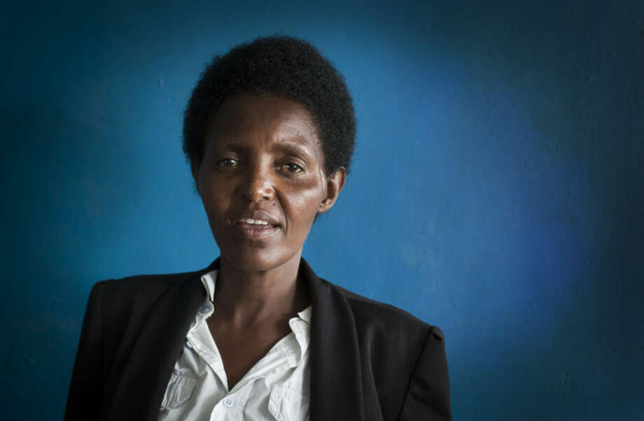 In this photo taken Wednesday, March 26, 2014, Alice Mukarurinda, poses for a photograph at her house in Nyamata, Rwanda. She lost her baby daughter and her right hand to a manic killing spree. Emmanuel Ndayisaba wielded the machete that took both. Yet today, despite coming from opposite sides of an unspeakable shared past, Alice Mukarurinda and Emmanuel Ndayisaba are friends. She is the treasurer and he the vice president of a group that builds simple brick houses for genocide survivors. They live near each other and shop at the same market. Their story of ethnic violence, extreme guilt and, to some degree, reconciliation is the story of Rwanda today, 20 years after its Hutu majority killed more than 1 million Tutsis and moderate Hutus. The Rwandan government is still accused by human rights groups of holding an iron grip on power, stifling dissent and killing political opponents. But even critics give President Paul Kagame credit for leading the country toward a peace that seemed all but impossible two decades ago. (AP Photo/Ben Curtis)