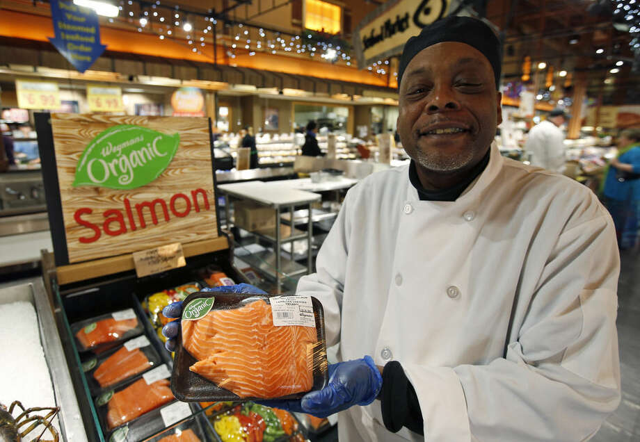 Cooking coach Chef Charles Hill poses for a picture as he holds a Canadian certified organic farm-raised King Salmon at the Wegmans, Friday, April 10, 2015 in Fairfax, Va. Organic fish is certified in the EU and Canada because the US doesn't have any standard. After more than a decade of delays, the government is moving toward allowing the sale of U.S.-raised organic fish and shellfish. But don't expect it in the grocery store anytime soon. (AP Photo/Alex Brandon)