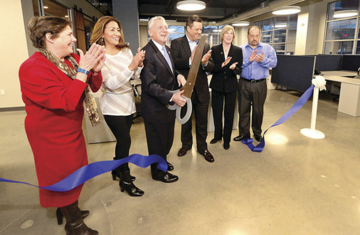 Hour photo/Erik Trautmann TeedCo COO Andrea Light, Lucia Rilling , Norwalk Mayor Harry Rilling, TeeDCo CEO, Shawn Teed, Norwalk Director of Economic Development Elizabeth Stocker, and TeeDCo Director of Sales Mark Ariano, cut the ribbon for the grand opening of their new offices on North Water Street last week.