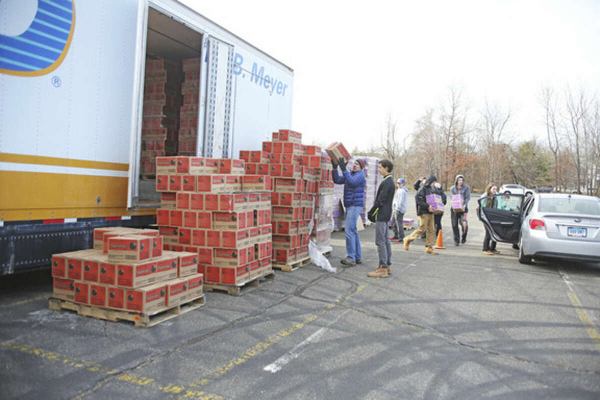 Hour photo/Danielle Calloway Mike Taetes grabs a box of Tagalongs to load into a car during a statewide cookie drop hosted by Girls Scouts of America at Norden Park in Norwalk Saturday morning.