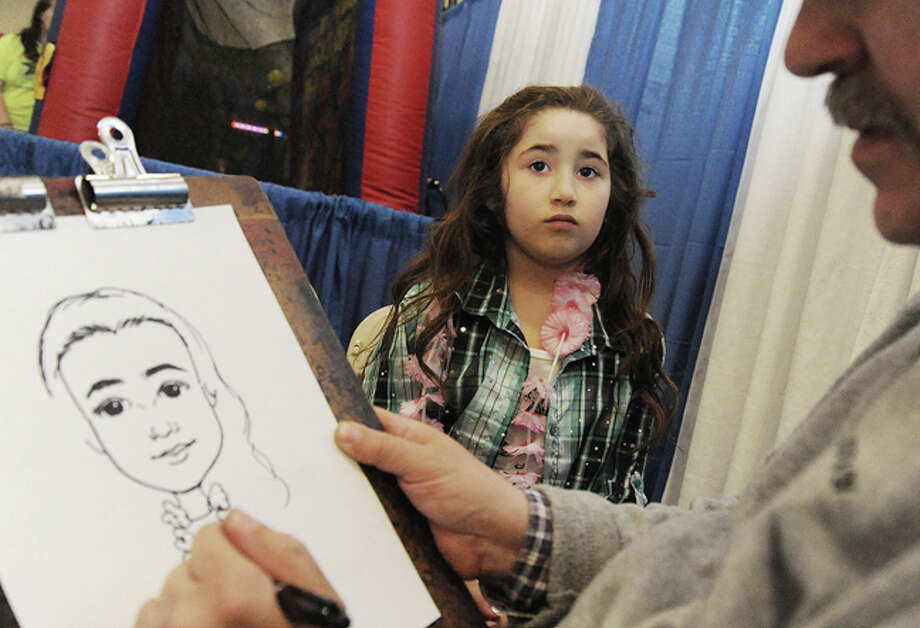 Leslie Rosara 7, getting her picture drawn by caricatures by Mike Valentine Sunday at the Kids Fest held in the Wilton High School field house. Hour photo/Matthew Vinci