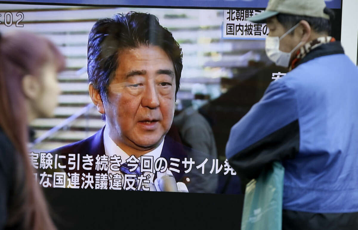 Passers-by look at a TV screen showing Japanese Prime Minister Shinzo Abe speak on North Korea's rocket launch, in Tokyo, Sunday, Feb. 7, 2016. North Korea on Sunday defied international warnings and launched a long-range rocket that the United Nations and others call a cover for a banned test of technology for a missile that could strike the U.S. mainland. (AP Photo/Eugene Hoshiko)
