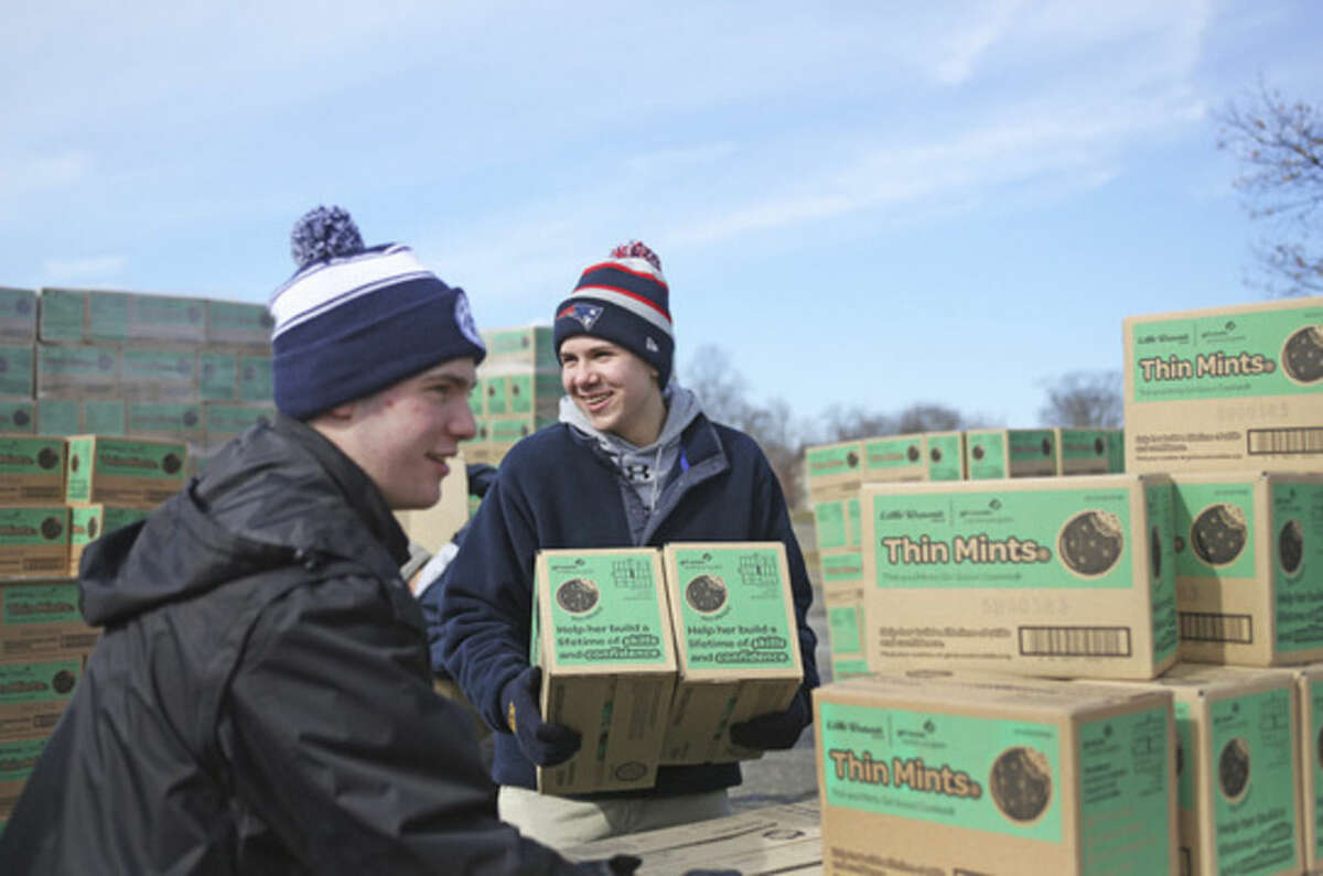 Dylan Warde picks up two boxes of Thin Mints to load into a car during a state wide cookie drop hosted by Girls Scouts of America at Norden Park in Norwalk Saturday morning. Hour Photo / Danielle Calloway