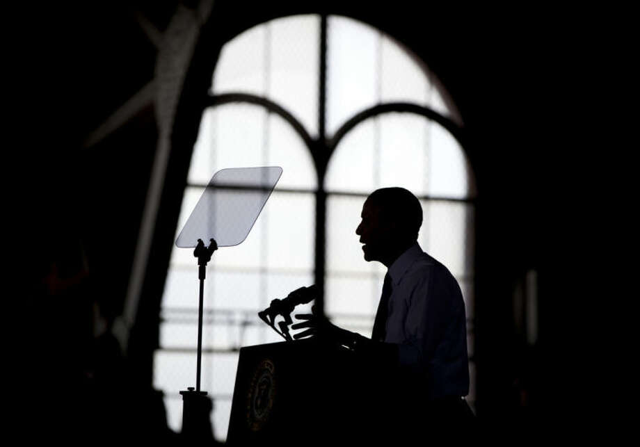 In this April 2, 2014, photo, President Barack Obama is silhouetted as he speaks at the University of Michigan, in Ann Arbor, Mich., about his proposal to raise the national minimum wage. The roller coaster of health care enrollment behind him, Obama is using a lull between foreign travel to refocus on his economic agenda, using executive actions to push for greater gender pay equality and to promote better technical skills for U.S. students.(AP Photo/Carolyn Kaster)